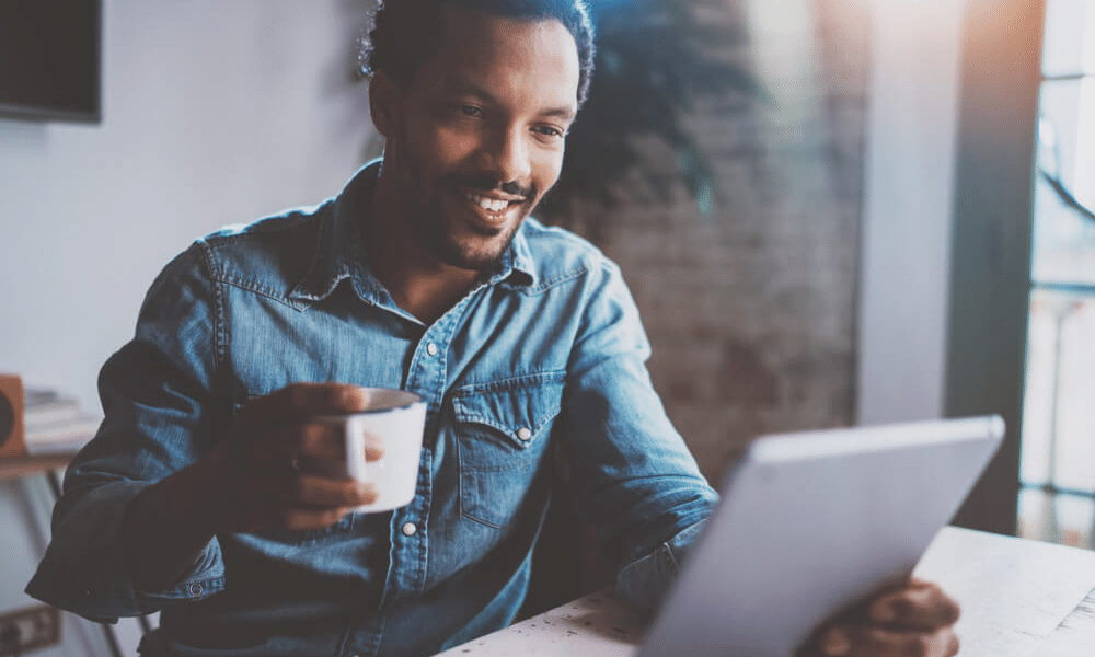 Man drinking coffee using tablet