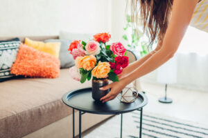 Woman putting flowers on coffee table
